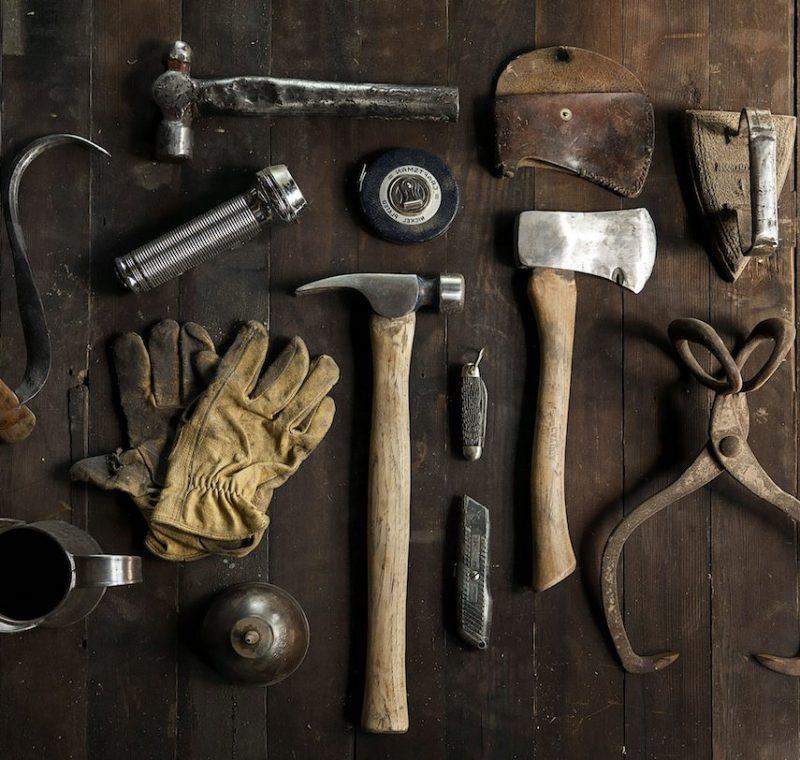 Werkzeuge wie Hammer, Handschuhe und Bügel liegen auf einen Holztisch